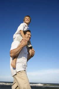 Caucasian father with pre-teen on shoulders on beach.